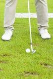 Club de golf que pone la bola en el agujero Foto de archivo