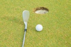 Club de golf que pone la bola en el agujero Fotos de archivo libres de regalías