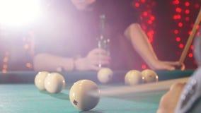 Club de los billares Una persona que juega billares Una señal que golpea la bola Una cerveza de consumición del hombre en el fond almacen de video