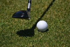 Club and Golf Ball. Approach shot into the green with a three wood, ball laying on beautiful green grass Stock Photos