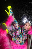 Club party blonde girl in acid anime style spandex catsuit with mirror car with pink fur ready for crazy clubbing life. Alone royalty free stock photography