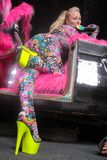 Club party blonde girl in acid anime style spandex catsuit with mirror car with pink fur ready for crazy clubbing life. Alone royalty free stock image