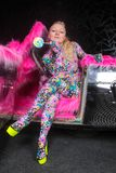 Club party blonde girl in acid anime style spandex catsuit with mirror car with pink fur ready for crazy clubbing life. Alone stock photos