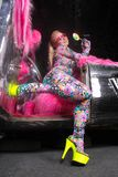 Club party blonde girl in acid anime style spandex catsuit with mirror car with pink fur ready for crazy clubbing life. Alone stock images