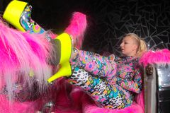Club party blonde girl in acid anime style spandex catsuit with mirror car with pink fur ready for crazy clubbing life. Alone royalty free stock images