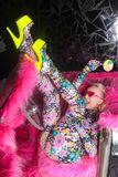 Club party blonde girl in acid anime style spandex catsuit with mirror car with pink fur ready for crazy clubbing life. Alone stock image