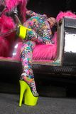 Club party blonde girl in acid anime style spandex catsuit with mirror car with pink fur ready for crazy clubbing life. Alone stock photo