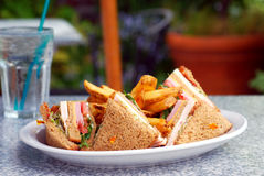 Club Sandwich. Plate with a club sandwich and French fries at an outdoor cafe royalty free stock images