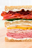 Club Sandwich. A classic club sandwich with ham, turkey, cheddar cheese, swiss cheese, lettuce, tomatoes, bacon, and lots of mayonnaise Stock Photography