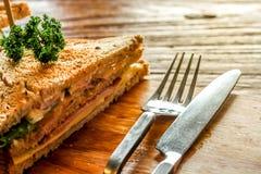 Club Sandwich auf der hölzernen Platte verzieren zusammen mit Gabel und adeln auf dem hölzernen Tabellenhintergrund der Barke Stockfotos