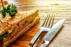 Club Sandwich auf der hölzernen Platte verzieren zusammen mit Gabel und adeln auf dem hölzernen Tabellenhintergrund der Barke Stockbild