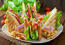 Club sandwich with cheese, cucumber, tomato, smoked meat and salami. Stock Photos