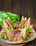 Club sandwich with cheese, cucumber, tomato, smoked meat and salami. Royalty Free Stock Images