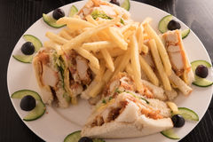 Club sandwich and french fries in a white plate. Stock Photos