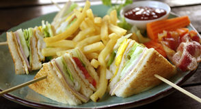 Club sandwich with fries and bacon Royalty Free Stock Photo