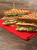 Club sandwich on napkin. Photo of a club sandwich made with turkey, bacon, ham, tomato, cheese, lettuce on a red napkin and old wood picnic table stock images