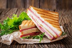 Club sandwich - panini with ham and cheese. On wooden background. Picnic food royalty free stock image