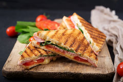 Club sandwich panini with ham. Tomato, cheese and basil royalty free stock photography