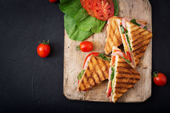 Club sandwich panini with ham. Tomato, cheese and basil. Flat lay. Top view stock images
