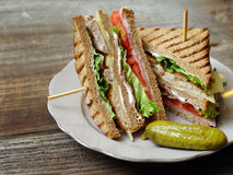 Club sandwich on a plate. Photo of a club sandwich made with turkey, bacon, ham, tomato, cheese, lettuce, and garnished with a pickle stock image
