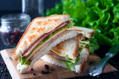 Club sandwich with a salad on a wooden plate Royalty Free Stock Photos