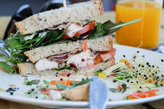 Club sandwich on a white plate. Club sandwich with vegetables, chicken and bacon on a white plate in focus Stock Photo
