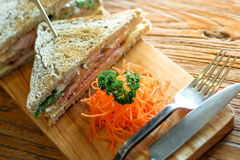 Club sandwich on the wood plate. Decorate with chopped carrot and parsley together with fork and knight on the bark wood table background Stock Images