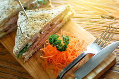 Club sandwich on the wood plate decorate with chopped carrot and parsley together with fork and knight on the bark wood table. Background Royalty Free Stock Images