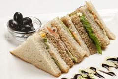 Club sandwiches. On a white plate with olives Royalty Free Stock Images