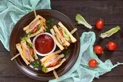 Club-sandwiches with crispy toast, sausage, cheese, tomato, greens. Traditional American snack Royalty Free Stock Photo