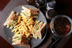 Club sandwiches with french fries and beer. Royalty Free Stock Image