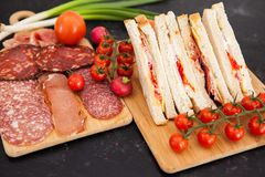 Club sandwiches next to cherry tomatoes, radish and green onion. On wooden boards Royalty Free Stock Photo