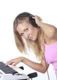 Clubbing. Young beautiful woman with headphones playing piano. Playing midi-keyboard. DJ-girl playing electronic music. Isolated on white Stock Photos
