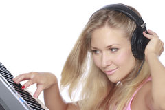 Clubbing. Young beautiful woman with headphones playing piano. Playing midi-keyboard. DJ-girl playing electronic music. Isolated on white Royalty Free Stock Photos