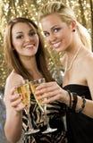 Clubbing Fun. Two beautiful young women enjoying champagne in a nightclub Royalty Free Stock Photos