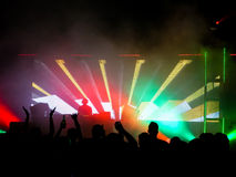 Clubbing scene. A colourful clubbing scene with a dj in the background and silhouettes of people in the forground royalty free stock photos