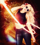 Clubbing trance girl dancing around 70s disco. Nightclub trance girl dancing around a 1970 disco club of bright lights, stars and glitter wearing sunglasses tank Stock Images