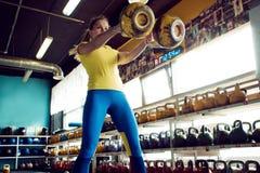 Clube de Kettlebell A menina está preparando-se para fazer um exercício com pesos, empurra o ciclo longo imagens de stock royalty free