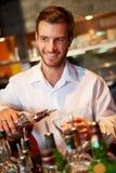 Clube noturno de Serving Drinks In do empregado de bar imagem de stock