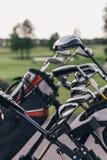 Clubes de golfe brilhantes em sacos de golfe fora Fotografia de Stock