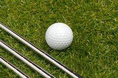 Clubes de golfe ou ferros do golfe com uma bola de golfe Imagens de Stock