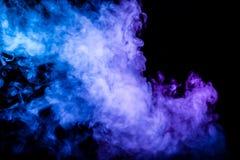 Clubes do fumo colorido da cor azul e cor-de-rosa em um fundo isolado preto sob a forma das nuvens macias fotos de stock royalty free