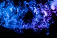 Clubes do fumo colorido da cor azul e cor-de-rosa em um fundo isolado preto sob a forma das nuvens do vape fotografia de stock royalty free