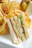 Clubhouse sandwich with potato chips. With cheese on top Stock Photo