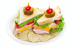 Clubhouse Sandwich. Topped with a pickle and a baby tomato and served with potato chips.  Shot on white background Royalty Free Stock Images