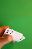 Clubs. Ace and king clubs in the hand on green background Royalty Free Stock Images