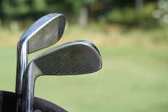 Clubs in Bag on Green. Closeup of golf clubs in bag against blurred background of golfcourse and woods. Horizontal format Royalty Free Stock Images