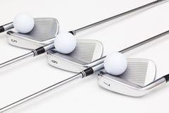 Clubs de golf titaniques sur la table blanche Photographie stock libre de droits
