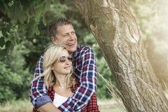 cluddling与他愉快的男朋友的年轻笑的妇女 库存照片