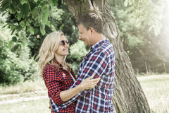 cluddling与他愉快的男朋友的年轻笑的妇女 免版税库存图片